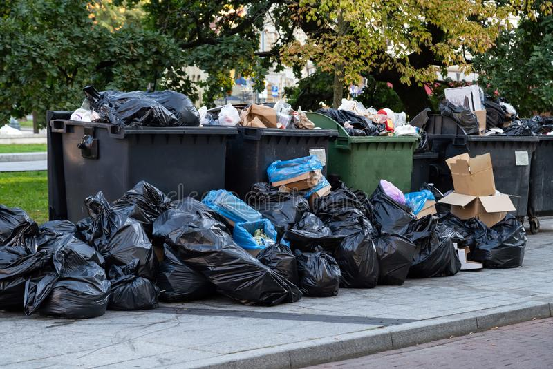 Huge garbage piles next to the dumpster after city fair. Stacks of litter bags overflow trash cans after festival in a city royalty free stock image