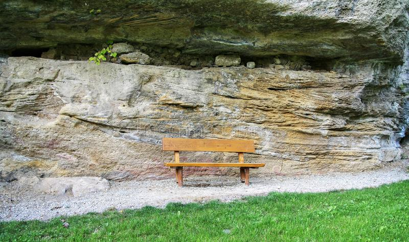 Huge geological layered rock from two-way pressures with wind erosion. Behind a bench and meadow stock photography