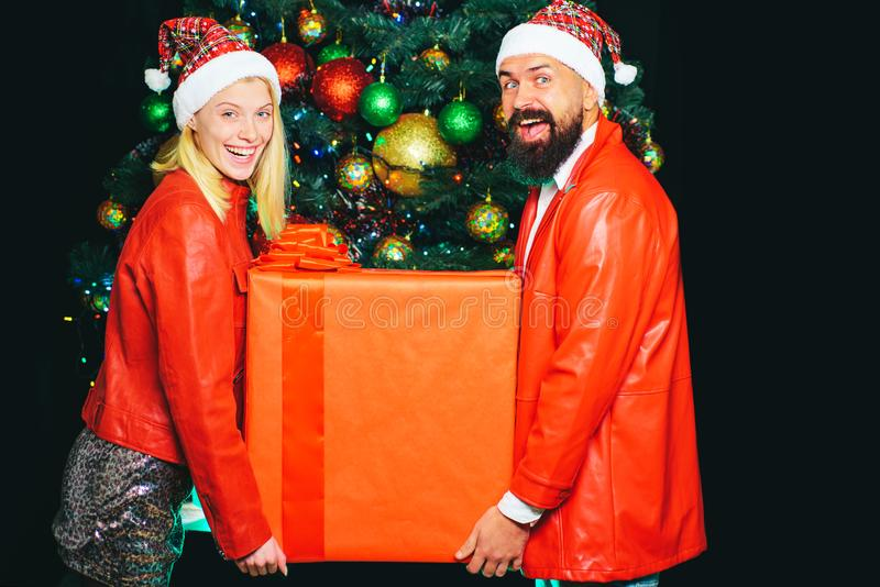 Huge gift for Christmas. A couple holds a big red box with a surprise. Happy New Year. Housewarming. Love and family royalty free stock photo