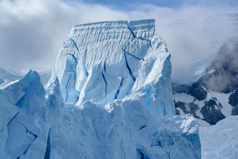 Huge glacier wall towering in Antarctica, majestic blue and white ice wall, Petzval Glacier, Paradise Bay, Antarctica royalty free stock photo