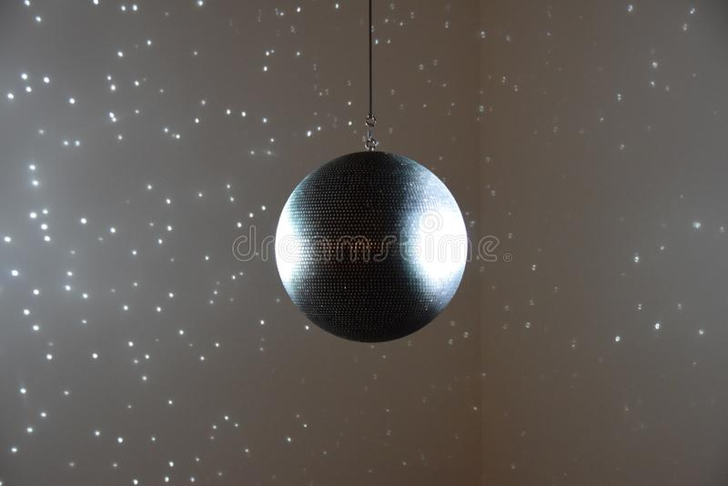 Huge glitter ball. Ceiling mounted glitter ball shining pinpoints of light on to the walls around it stock photo