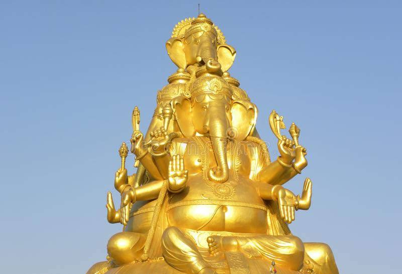 Huge golden color statue of Lord Ganesha with 3 faces royalty free stock images