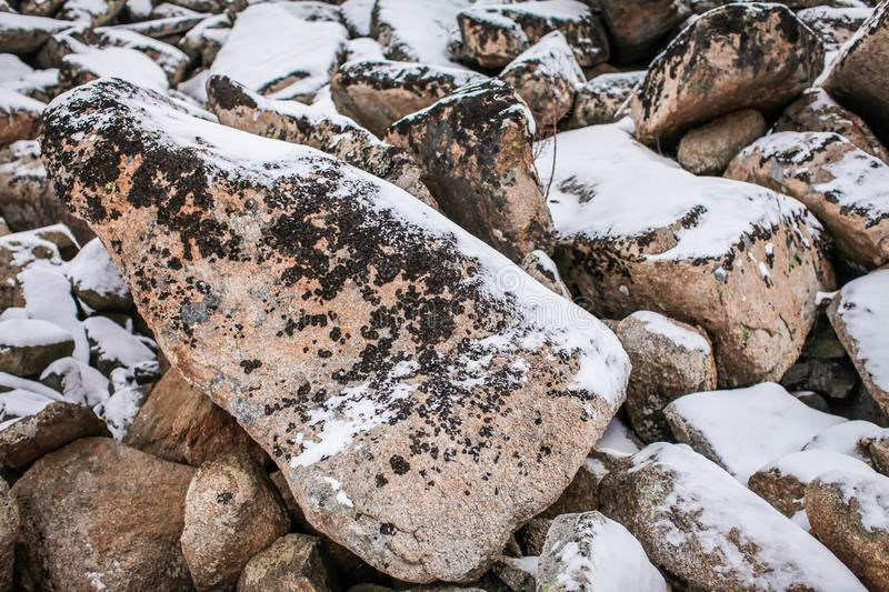 Huge granite boulders stones in the snow in different shapes and sizes, stone natural winter background stock photos