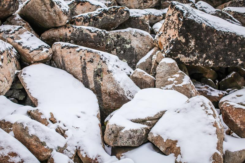 Huge granite boulders stones in the snow in different shapes and sizes, stone natural winter background royalty free stock photos