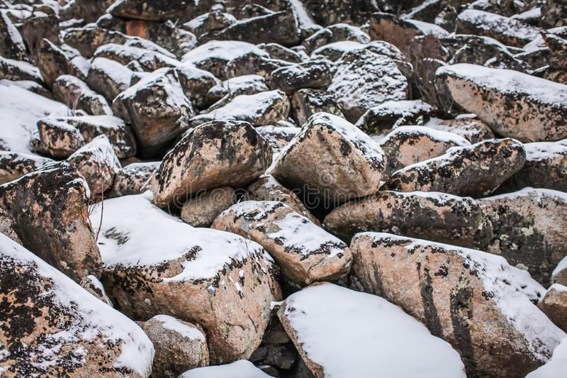 Huge granite boulders stones in the snow in different shapes and sizes, stone natural winter background stock photography