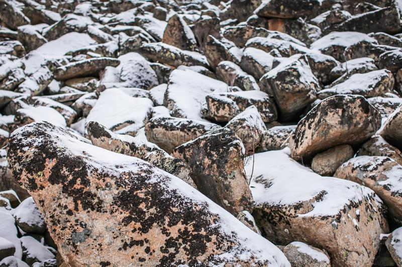 Huge granite boulders stones in the snow in different shapes and sizes, stone natural winter background stock image