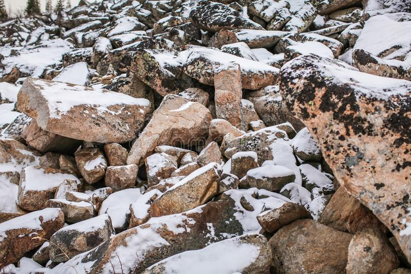 Huge granite boulders stones in the snow in different shapes and sizes, stone natural winter background stock photo