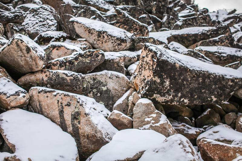 Huge granite boulders stones in the snow in different shapes and sizes, stone natural winter background royalty free stock images