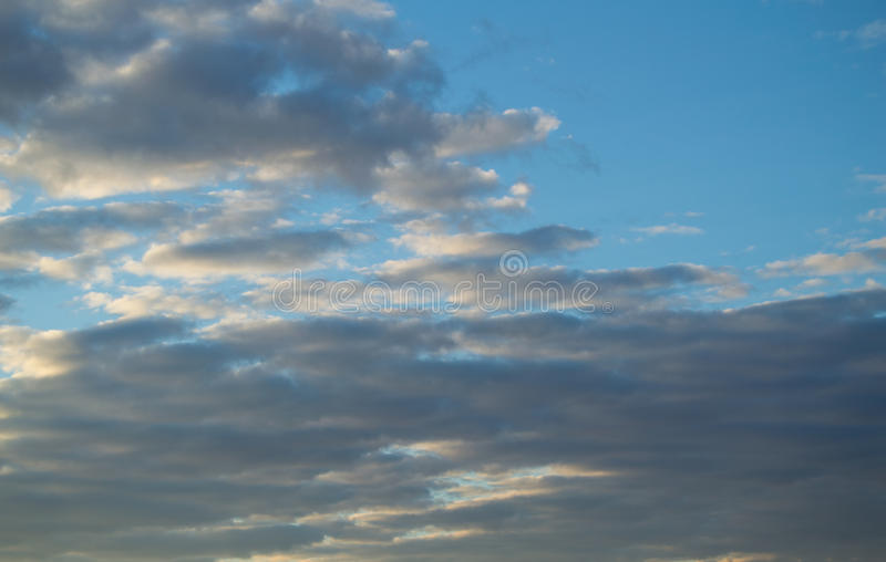 Huge gray clouds in the blue sky at sunset after rain, background stock photography