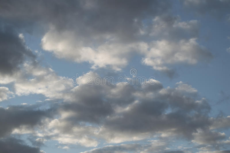 Huge gray clouds in the blue sky at sunset after rain, background royalty free stock images
