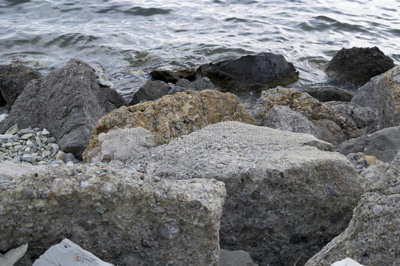 Huge gray rocks on the sea shore. Water on the background. Beautiful holiday background royalty free stock photo