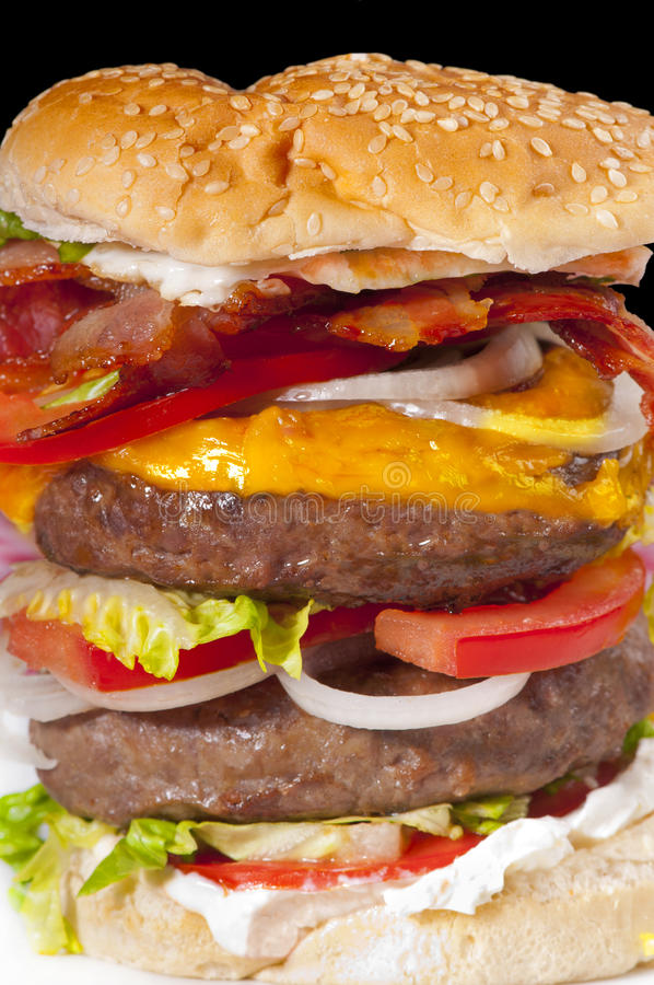 Huge hamburger. Giant double hamburger with tomato slices, cheese, cream cheese, bacon, egg, lettuce and onion in a white bread bun stock photos