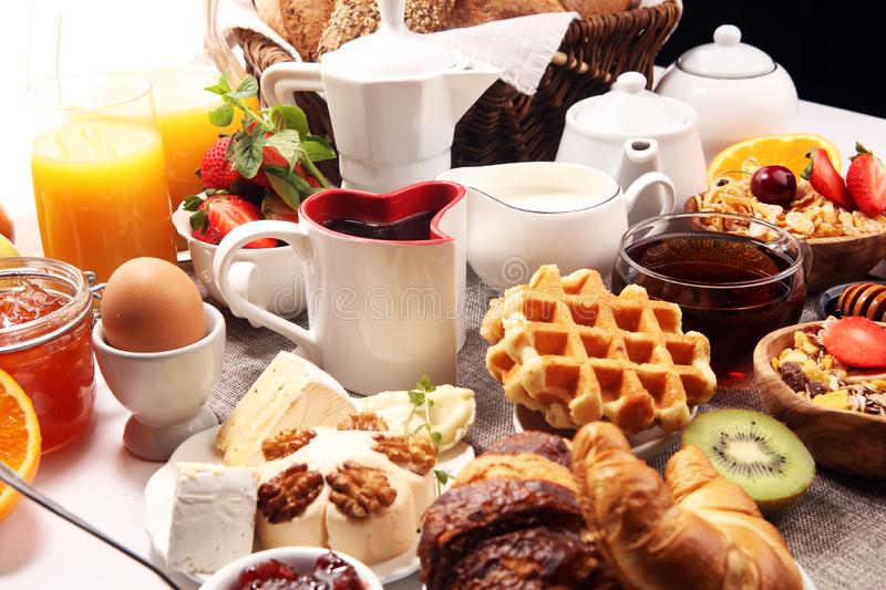 Huge healthy breakfast on table with coffee, orange juice, fruits, waffles and croissants. Good morning concept stock photography