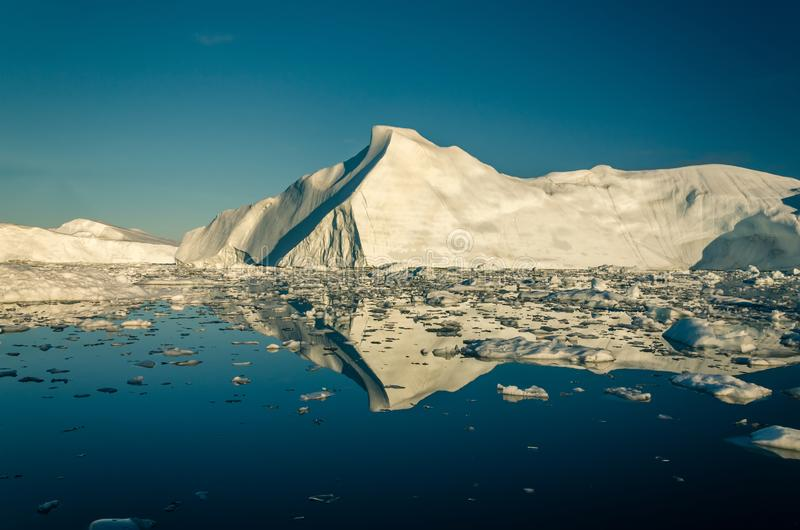 Huge iceberg in the Ilulissat icefjord and ice field reflects in the water. Greenland, icebergs, icy, frozen, freezing, sea, ocean, blue, golden, light, large stock photo