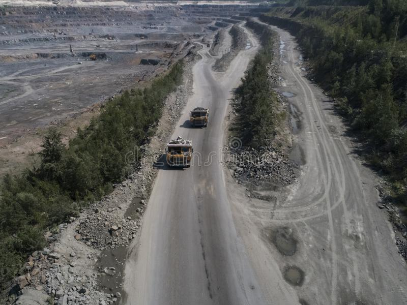 Huge industrial dump truck in a stone quarry loaded transporting marble or granite shot from a drone top shot stock photos