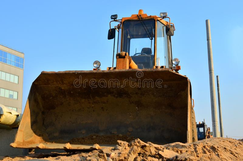 Huge iron bucket front loader at a construction site stock images