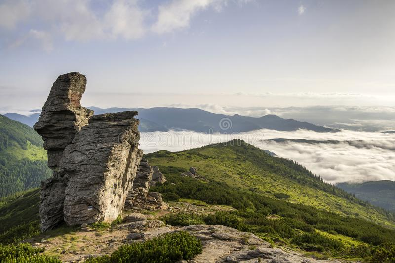 Huge limestone rocky boulder on green mountain top on background of valley filled with white puffy clouds and fog, view of covered. With evergreen forest royalty free stock photos