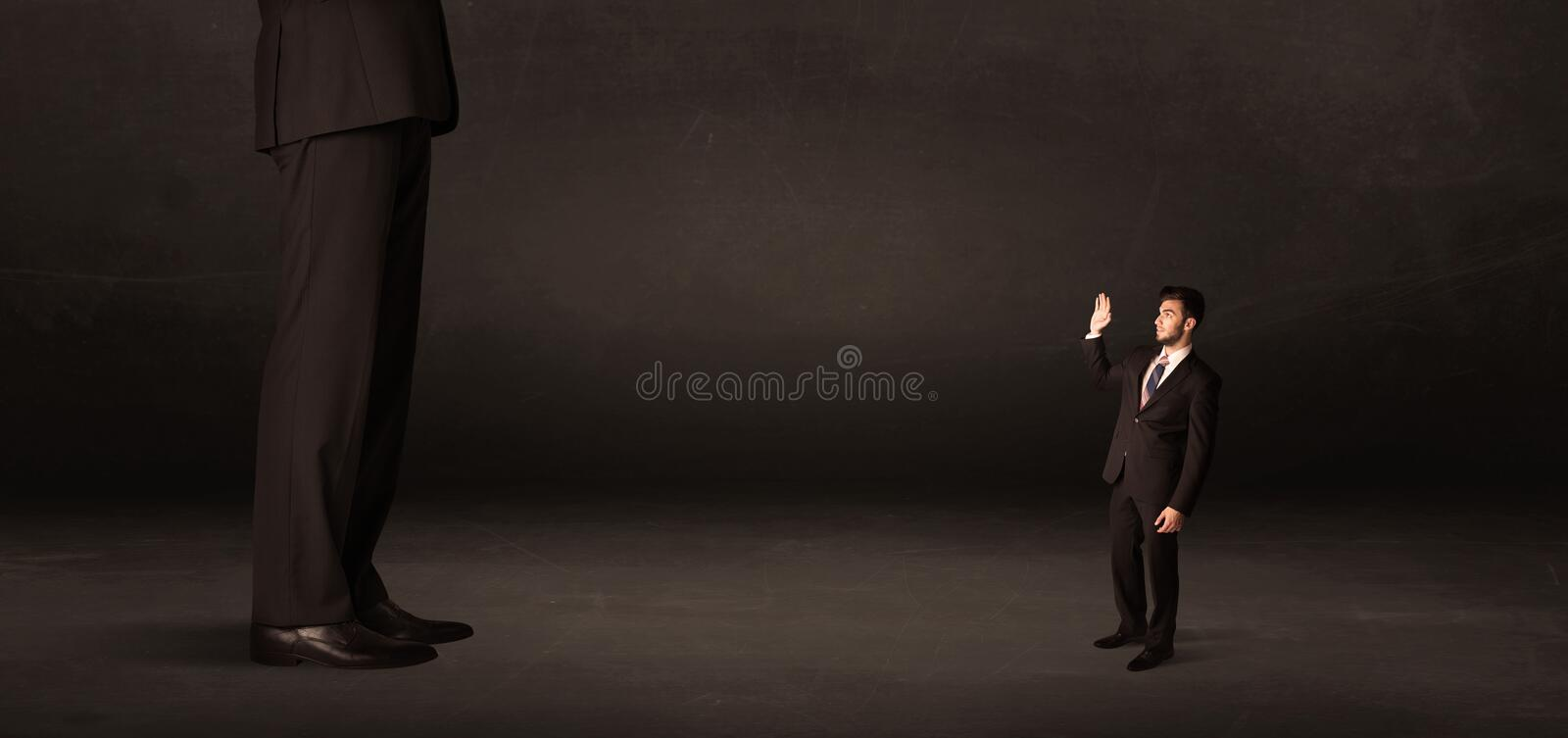 Huge man with small businessman standing at front concept. On background royalty free stock image