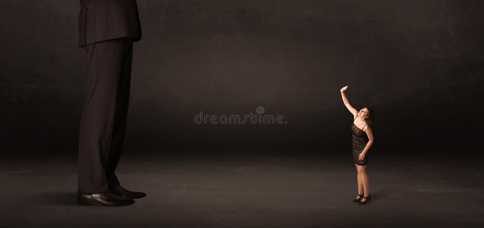 Huge man with small businesswoman standing at front concept. On background stock photos