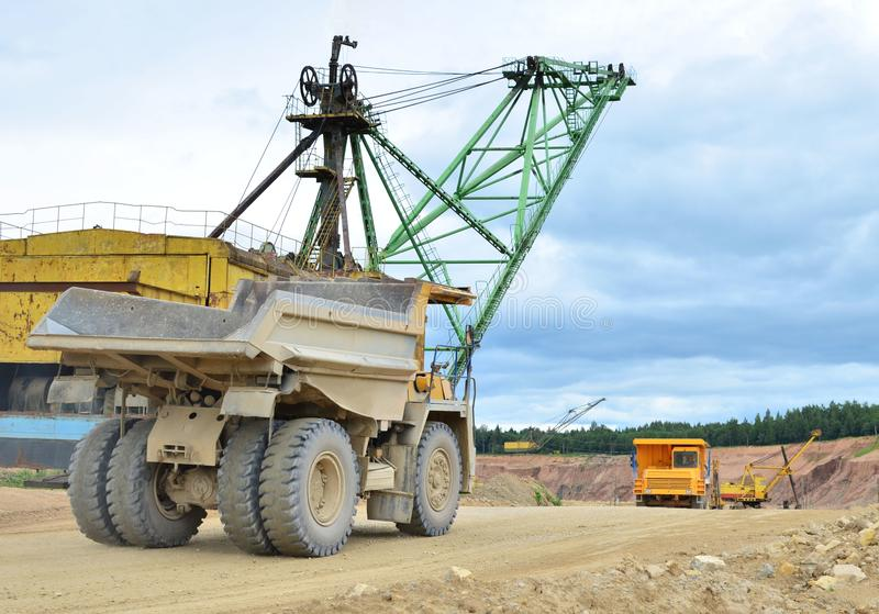 Huge mining excavator and dump trucks work in an open pit. Loading and transportation of sand, gravel, dolomite and limestone to the place of processing and royalty free stock photos
