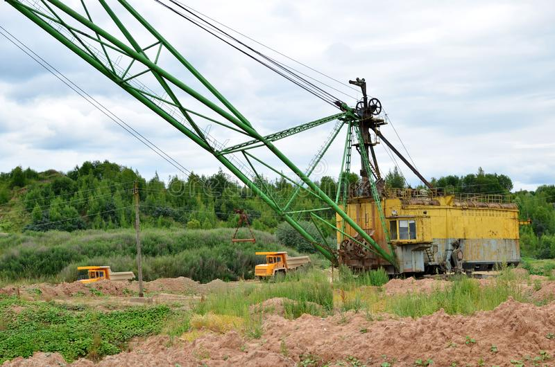 Huge mining excavator and dump trucks work in an open pit. Loading and transportation of sand, gravel, dolomite and limestone to the place of processing and stock photos