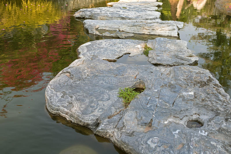 Huge natural step stone path way to walk on water pond garden at. The park in afternoon royalty free stock photos