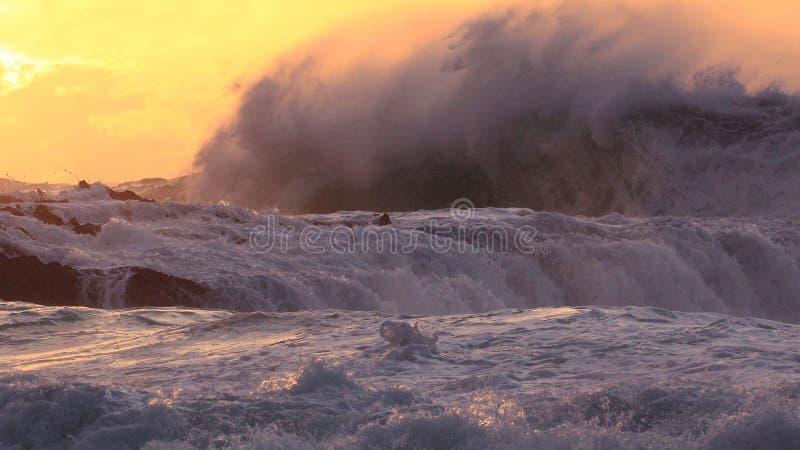 Huge ocean surf crashing over rocks at sunset stock images