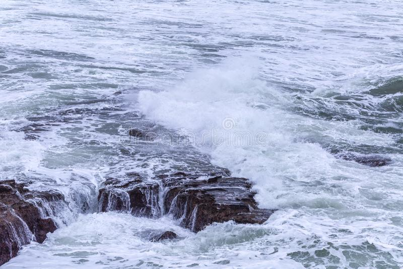 A huge ocean waves breaking on the coastal cliffs in at the cloudy stormy day. Breathtaking romantic seascape of ocean coastline stock photo