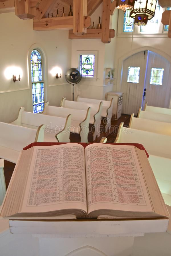 Beautiful old Bible opened to John. A huge old bible opened to the Book of John rests on a pulpit in a small chapel stock photos