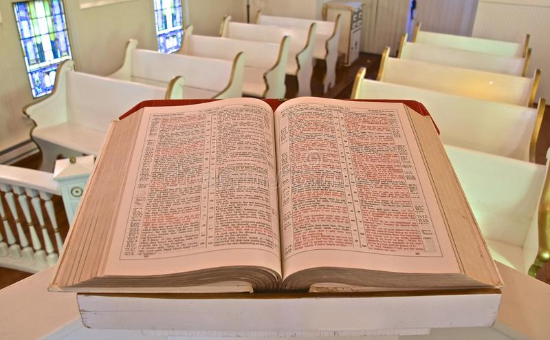 Beautiful old Bible opened to John. A huge old bible opened to the Book of John rests on a pulpit in a small chapel royalty free stock photo