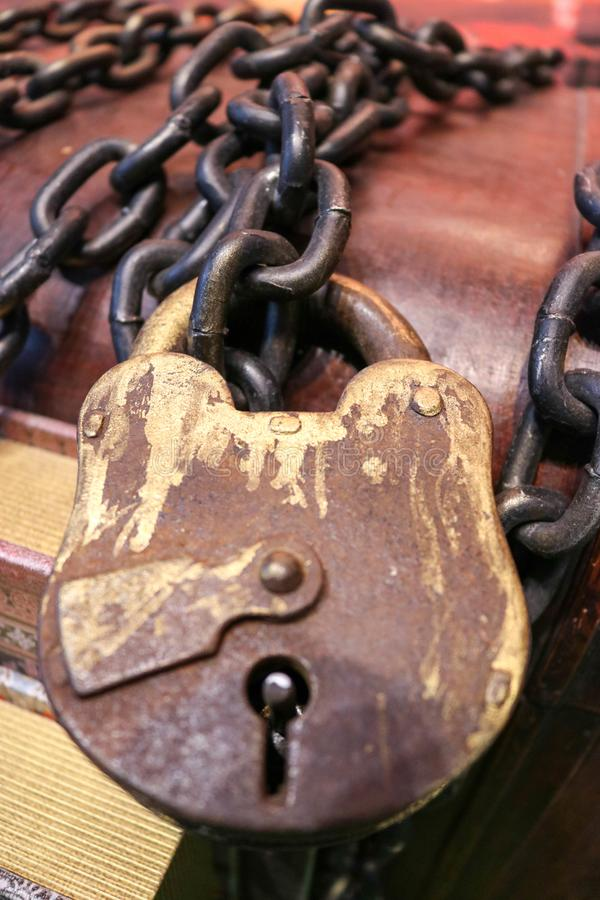 A huge old brown lock tied with thick, strong metal chains stock image