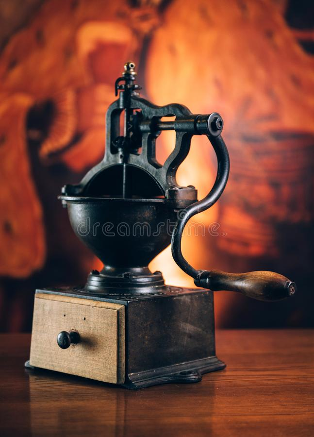 Huge old coffee grinder on wooden table. Vintage toned royalty free stock photography