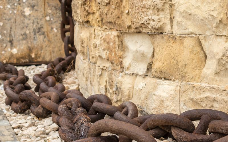A huge, old and rusty chain hanging down from sandstone wall in Fort St. Elmo, Valletta, Malta royalty free stock photo