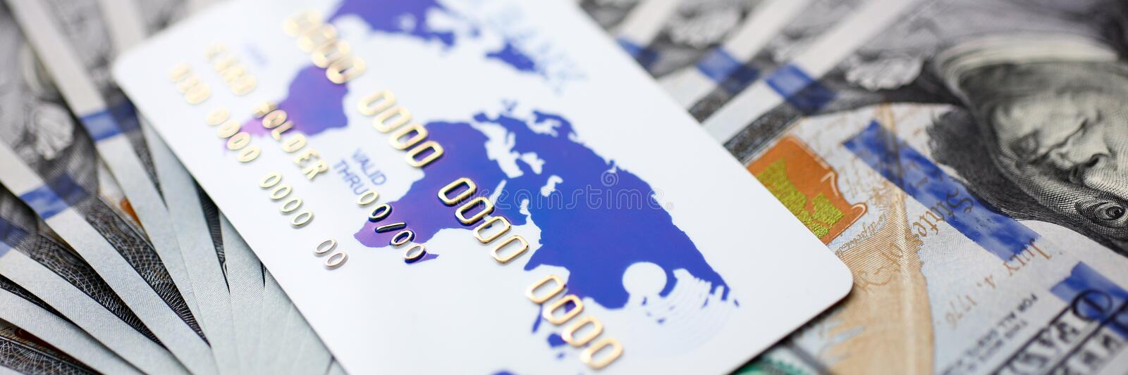 Huge pack of US money and bank card lying down on important financial document. Macro stock photo