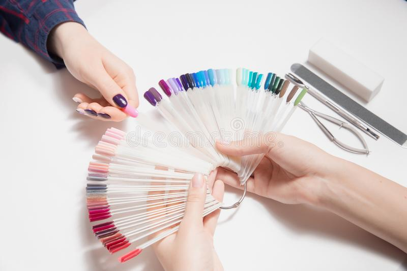A huge palette of colors gel nail Polish in beauty salon. Hard choice. Nice manicure. Well-groomed woman`s hands. royalty free stock photos