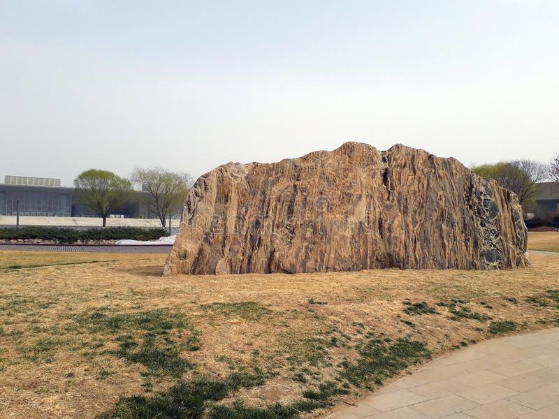 Huge piece of rock in the park. Tianjin, China. Huge piece of rock in the park among the rotten grass, early spring. Tianjin, China royalty free stock image