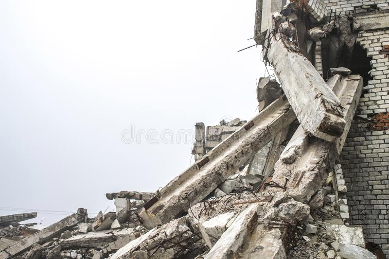 A huge pile of gray concrete debris from piles and stones of the destroyed building. Copy space. A huge pile of gray concrete debris from piles and stones of the royalty free stock images
