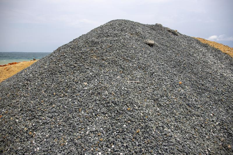 Huge pile of grey gravel on coast. Construction site material. Big gravel heap outdoor. Construction supply closeup. royalty free stock photo