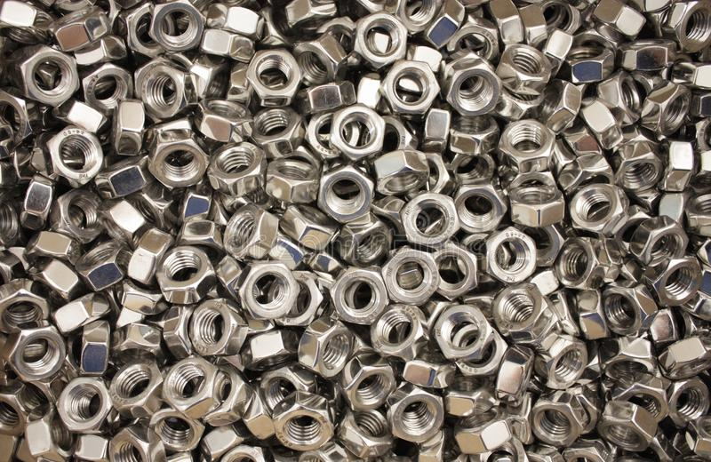 A huge pile of metal nuts. A large number of metal nuts in the heap form various different patterns and glare