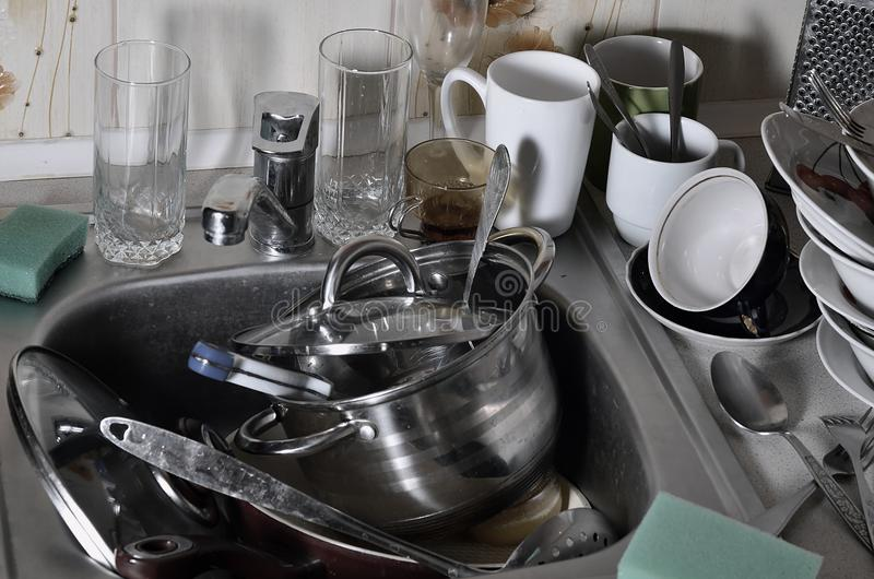 A huge pile of unwashed dishes in the kitchen sink and on the countertop. A lot of utensils and kitchen appliances before washing royalty free stock images