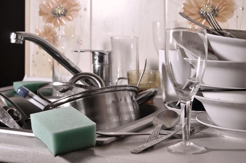 A huge pile of unwashed dishes in the kitchen sink and on the countertop. A lot of utensils and kitchen appliances before washing. The concept of daily cooking royalty free stock photo
