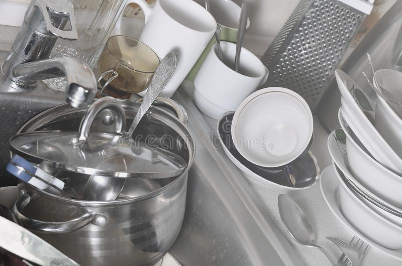 A huge pile of unwashed dishes in the kitchen sink and on the countertop. A lot of utensils and kitchen appliances before washing. The concept of daily cooking stock image