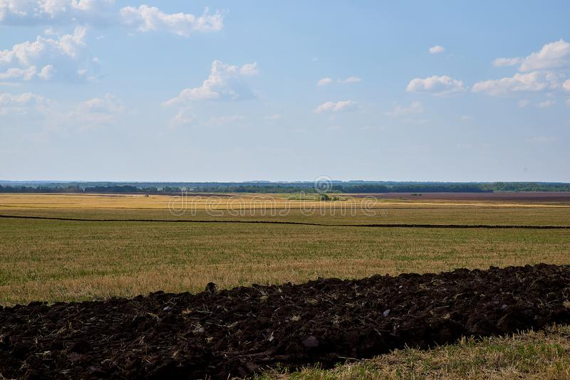 Huge ploughed village field against summer sky. royalty free stock photography