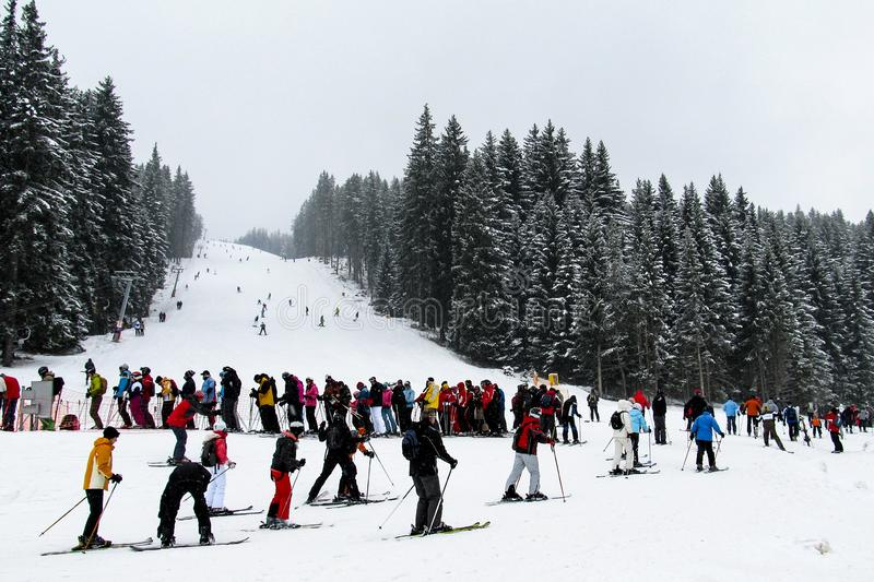 A huge queue of skiers on the ski lift on the background of the ski slopes. Bulgaria, Bansko-03 January 2011. A huge queue of skiers on the ski lift on the royalty free stock photos