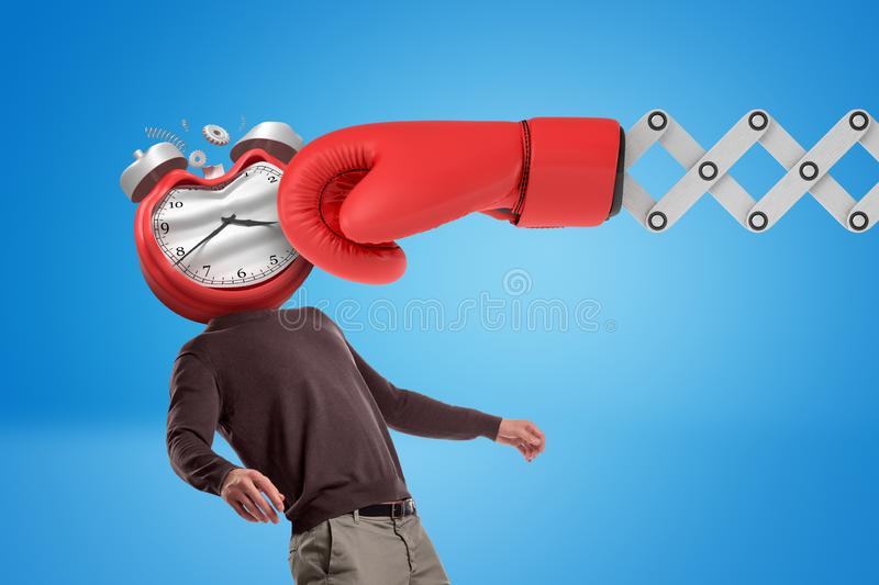Huge red boxing glove punching man with an alarm clock instead of his face on blue background. stock photo