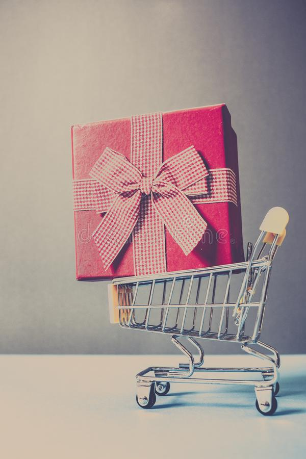 Huge red gift box in shopping cart - online shopping. Background, basket, birthday, business, buy, carry, christmas, colorful, commerce, commercial, concept royalty free stock image