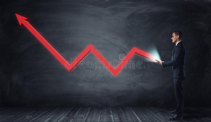 Huge red line graph with an upturned arrow growing from a businessman hands. Generating success. Stimulating progress. Growth of incomes stock photography