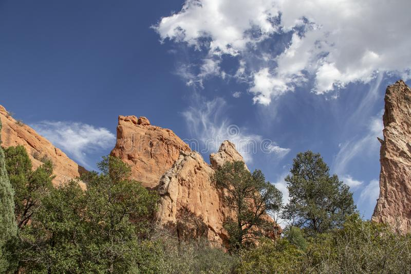 Huge red rocks jutting out of the ground from among the trees beneath a dramatic blue sky with clouds in Garden of the Gods near. Colorado Springs USA royalty free stock image