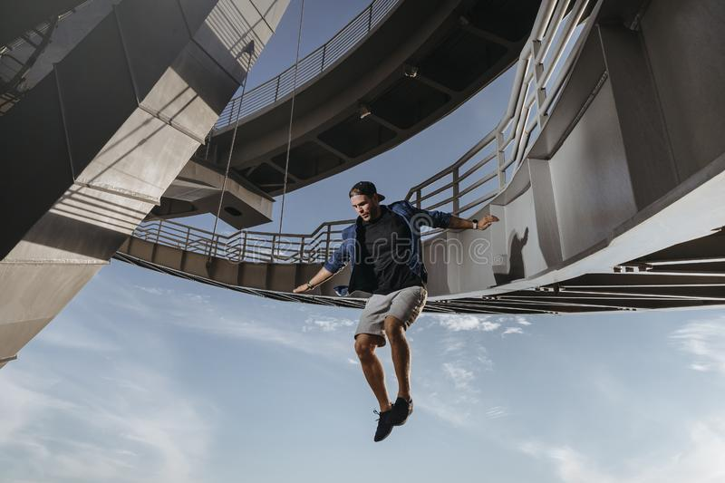 Huge and risky jump from a bridge performed by parkour athlete. Freedom in Freerunning stock photos