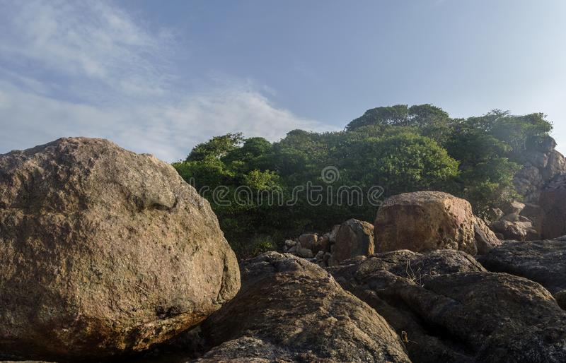 Huge rocks at the beautiful tropical beach located at the island near ocean stock images
